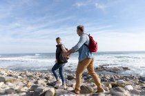 Side view of an adult Caucasian couple enjoying free time walking on a beach and smiling beside the sea on a sunny day — Stock Photo