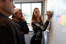 Vista frontal de una joven mujer caucásica que trabaja en una oficina creativa, escribiendo en una pizarra blanca con sus colegas caucásicos masculinos mirando . - foto de stock