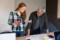 Vista frontale di una giovane donna caucasica e di un uomo caucasico che lavora in uno studio creativo, accanto a una scrivania, guardando i progetti architettonici . — Foto stock