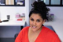 Porträt einer jungen Frau mit gemischter Rasse, die an einem Schreibtisch in einem kreativen Büro sitzt und in die Kamera lächelt. — Stockfoto