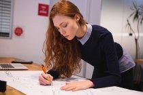 Vue latérale d'une jeune femme caucasienne travaillant dans un bureau créatif, s'appuyant sur son bureau et prenant des notes sur papier — Photo de stock