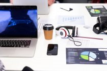 Високий кут огляду столу у творчому офісі з ноутбуком, смартфоном, навушниками та чашкою кави.. — стокове фото
