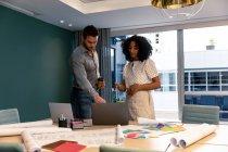 Vista frontale di un giovane professionista caucasico e di una donna mista che lavora in un ufficio moderno, in piedi su una scrivania usando un computer portatile e parlando — Foto stock