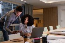 Vista frontale di un giovane professionista caucasico e di una donna di razza mista che lavorano fino a tardi in un ufficio moderno presso una scrivania, usando un computer portatile e guardando insieme un tablet — Foto stock