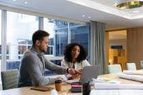 Вид сбоку на молодого кавказского профессионального мужчину и женщину смешанной расы, работающую в современном офисе, сидящую за столом с помощью ноутбука — стоковое фото