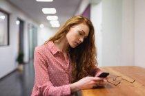 Бічний погляд на молоду кавказьку жінку, яка працює в творчому офісі за допомогою смартфона. Це початковий бізнес. — стокове фото