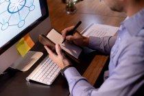 Vue de côté gros plan d'un jeune professionnel caucasien travaillant tard dans un bureau moderne, assis à un bureau à l'aide d'un ordinateur de bureau et prenant des notes — Photo de stock