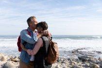 Vista frontale di una coppia caucasica adulta di mezza età che si gode il tempo libero baciandosi accanto al mare in una giornata di sole — Foto stock
