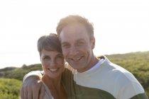 Retrato de um feliz e pacífico casal adulto de meia-idade caucasiano desfrutando de tempo livre sorrindo para a câmera em um dia ensolarado . — Fotografia de Stock