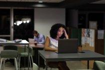 Vista frontale di una giovane donna professionista di razza mista e uomo caucasico che lavora fino a tardi in un ufficio moderno, donna seduta a una scrivania con un computer portatile e un uomo seduto sullo sfondo — Foto stock