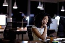 Бічний вид на молоду змішану расу професійну жінку, яка працює в сучасному офісі, сидячи за столом, використовуючи настільний комп'ютер. — стокове фото