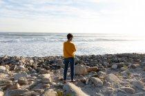 Вид сзади на кавказскую женщину, наслаждающуюся свободным временем на пляже у моря в солнечный день она смотрит на океан — стоковое фото