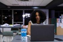 Vista frontal de una joven profesional de raza mixta que trabaja hasta tarde en una oficina moderna, sentada en un escritorio con un café para llevar usando una computadora portátil - foto de stock