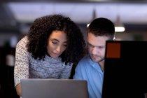 Vista frontal de cerca de un joven hombre profesional caucásico y una mujer de raza mixta que trabajan hasta tarde en una oficina moderna en un escritorio usando una computadora portátil juntos — Stock Photo