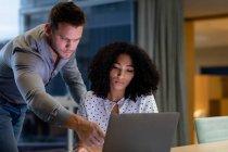Vue de face d'un jeune homme professionnel de race blanche et d'une femme de race mixte travaillant tard dans un bureau moderne à l'aide d'un ordinateur portatif, l'homme se tenant debout et pointant vers l