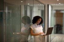 Vue de face d'une jeune professionnelle métisse travaillant tard dans un bureau moderne, debout dans le couloir à l'aide d'un ordinateur portable, reflétée dans un mur de verre — Photo de stock
