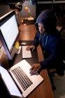 Vista de ángulo alto de una joven mujer de raza mixta con una sudadera con capucha que trabaja hasta tarde en una oficina moderna, sentada en un escritorio usando una computadora portátil y una computadora de escritorio - foto de stock