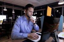 Vista frontal de un joven profesional caucásico que trabaja hasta tarde en una oficina moderna, sentado en un escritorio usando una computadora de escritorio — Stock Photo