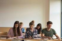 Estudiantes estudiando en el escritorio en el aula - foto de stock
