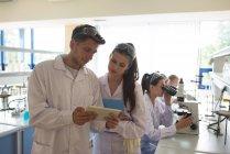 Homme étudiant montrant tablette à un ami tout en se tenant debout dans le laboratoire — Photo de stock