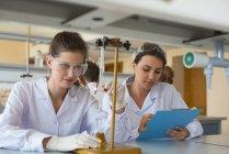 Estudiantes universitarias practicando experimento de química en laboratorio - foto de stock