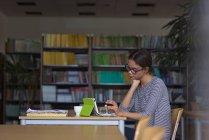 Estudiante universitaria usando tableta digital mientras está sentada en el escritorio en el aula - foto de stock