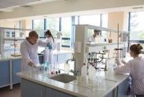 Estudiantes universitarios practicando experimento en laboratorio - foto de stock