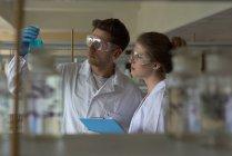 Jóvenes estudiantes universitarios que practican el experimento de química en laboratorio - foto de stock