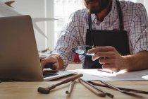 Partie médiane de l'artisan utilisant un ordinateur portable au bureau — Photo de stock