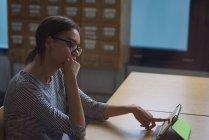 Estudiante adolescente usando tableta digital en el escritorio en el aula - foto de stock