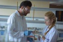 Estudiantes universitarios atentos haciendo un experimento en laboratorio - foto de stock
