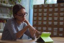 Adolescente universitaria usando tableta digital en el escritorio en el aula - foto de stock