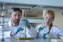 Estudiantes universitarios atentos haciendo un experimento químico en laboratorio - foto de stock