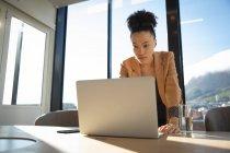 Una donna d'affari mista che lavora in un ufficio moderno, accanto a una scrivania e usando un computer portatile, in una giornata di sole — Foto stock