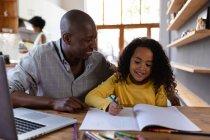 Vista frontal de cerca de un hombre afroamericano en casa, sentado en una mesa con su hija pequeña mirándola dibujar en un libro escolar y ambos sonriendo, una computadora portátil en la mesa frente a él - foto de stock