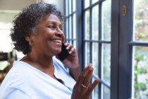 Femme de race mixte âgée profitant de son temps à la maison, de la distance sociale et de l'isolement personnel en quarantaine, regardant par une fenêtre, parlant sur un smartphone — Photo de stock