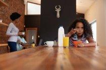Vista frontal de una joven afroamericana en casa en la cocina, sentada en una mesa comiendo cereales para el desayuno, su padre sentado usando una computadora portátil y su madre de pie junto a él en el fondo - foto de stock