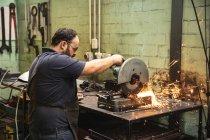 Trabajadores caucásicos de la fábrica que usan delantal oscuro y gafas de seguridad, de pie en un banco de trabajo y cortando metal en un taller. - foto de stock