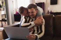 Передній погляд Кавказької пари чоловіків відпочиває вдома, сидячи на дивані, обіймаючи, спілкуючись за допомогою ноутбука. — стокове фото
