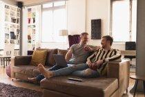 Передній вид на кавказьке подружжя чоловіків відпочиває вдома, сидячи на дивані, розмовляючи і посміхаючись, тримаючи в руках чашечки напою, використовуючи ноутбук. — стокове фото