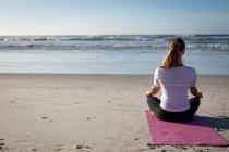 Задний вид на кавказку, занимающуюся спортом на пляже в солнечный день, практикующую йогу, сидящую в позе йоги, медитирующую в позе лотоса, стоящую лицом к морю. — стоковое фото