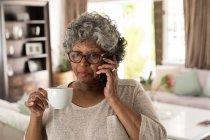 Une femme afro-américaine âgée passe du temps à la maison, à prendre des distances sociales et à s'isoler en quarantaine pendant l'épidémie de coronavirus covid 19, parlant sur un smartphone et tenant une tasse — Photo de stock