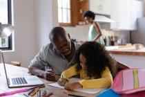 Vista frontal de un hombre afroamericano en casa, sentado en una mesa con su hija pequeña mirándola dibujar en un libro escolar, una computadora portátil en la mesa frente a él, con la madre de pie en la cocina en el fondo - foto de stock