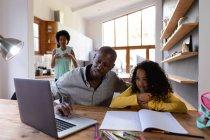 Vista frontal de un hombre afroamericano en casa, sentado en una mesa con su hija pequeña mirando un ordenador portátil juntos, un libro escolar en la mesa frente a ella, con la madre de pie en la cocina en el fondo - foto de stock