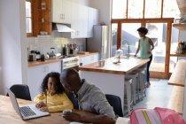 Vista de alto ángulo de un hombre afroamericano en casa, sentado en una mesa con su hija pequeña mirando un ordenador portátil juntos y hablando, con la madre de pie en la cocina en el fondo - foto de stock