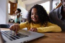 Vista frontal de cerca de una joven afroamericana en casa, sentada en una mesa con su padre mirando un ordenador portátil juntos, la niña presionando el teclado del ordenador y sonriendo, con la madre de pie en la cocina en el fondo - foto de stock