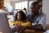 Vista frontal de cerca de una joven afroamericana en casa, sentada en una mesa con su padre mirando un ordenador portátil juntos, el padre presionando el teclado del ordenador y sonriendo, con la madre de pie en la cocina en el fondo - foto de stock