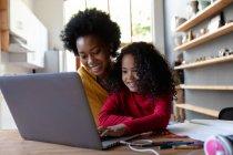 Vista frontal de cerca de una joven afroamericana en casa, sentada en una mesa con su madre mirando un ordenador portátil juntos, la hija presionando el teclado del ordenador y ambos sonriendo - foto de stock