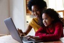Vista lateral de cerca de una joven afroamericana en casa, sentada en una mesa con su madre mirando un ordenador portátil juntos, la hija presionando el teclado del ordenador y ambos sonriendo - foto de stock
