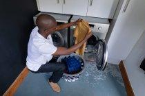 Vue en angle élevé d'un Afro-Américain à la maison, s'agenouillant et sortant la lessive d'une machine à laver — Photo de stock